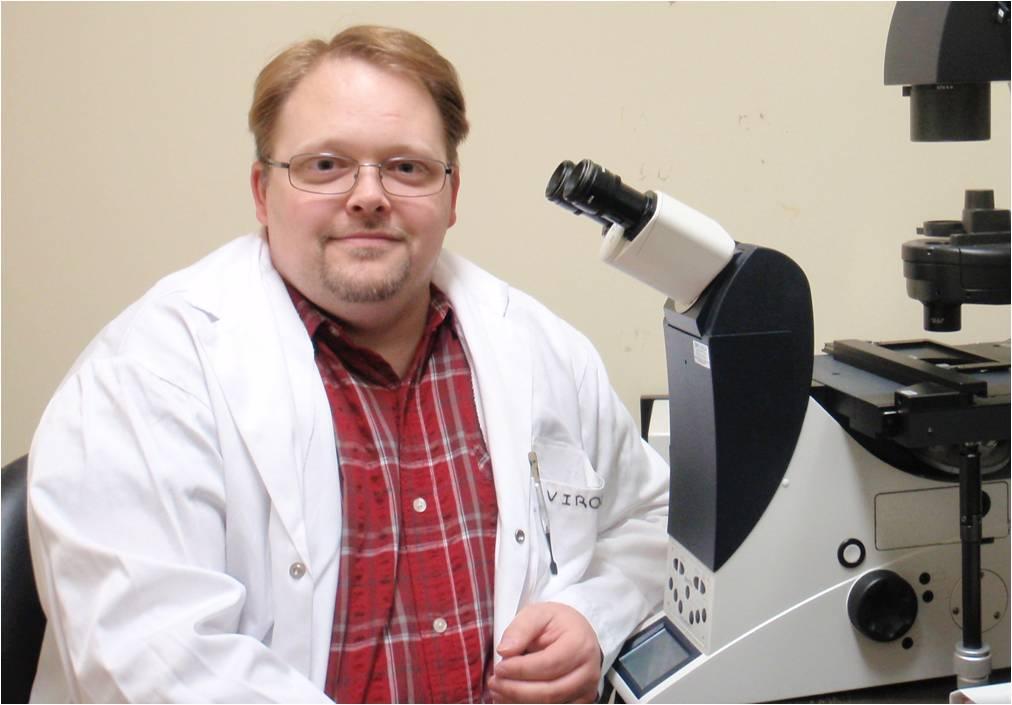 Le Dr Gagnon travaillant au microscope inversé à fluorescence.