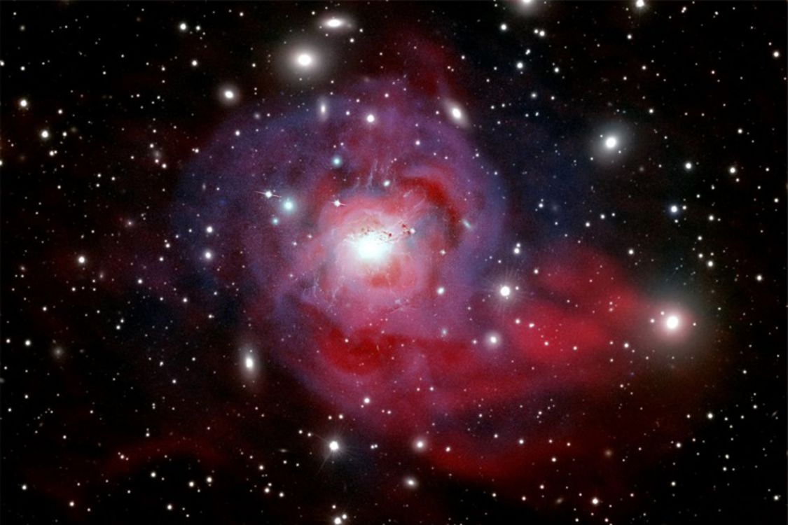 Au centre de l'amas de Persée trône la spectaculaire galaxie NGC 1275, où se cache un trou noir supermassif responsable de puissants jets de particules (en rose). Éjectées bien au-delà de la galaxie, ces particules entretiendraient la température incroyablement élevée (60 millions de degrés Celsius) des gaz qui s'étendent entre les galaxies (en bleu).